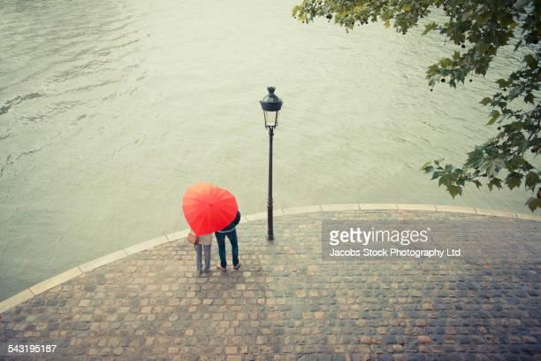 Caucasian couple standing under heart shape umbrella