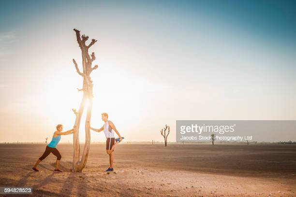 Caucasian couple stretching in desert