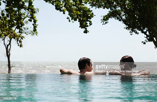 Caucasian couple swimming in infinity pool together