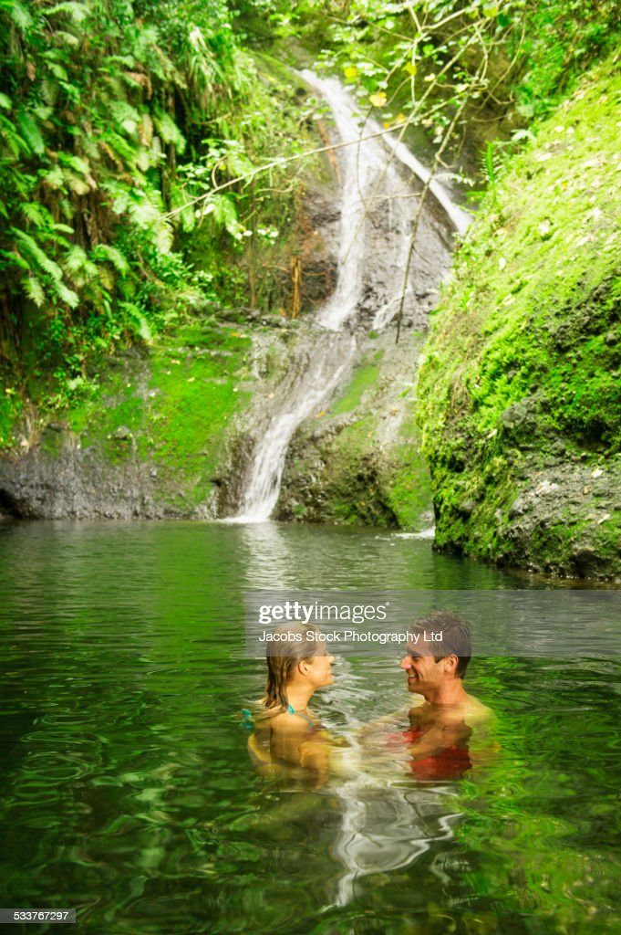 Caucasian couple swimming in remote jungle pool : Foto stock