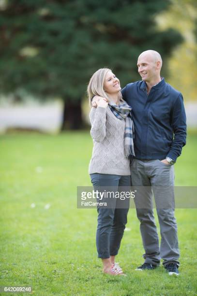 caucasian couple taking a walk in the park - mid adult couple stock pictures, royalty-free photos & images