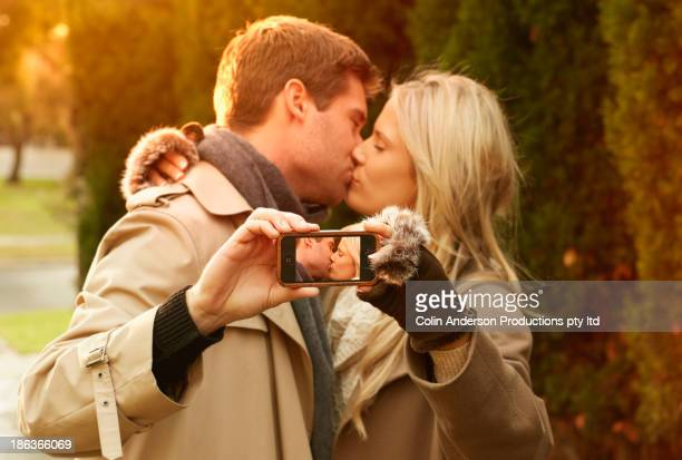 Caucasian couple taking picture of themselves kissing