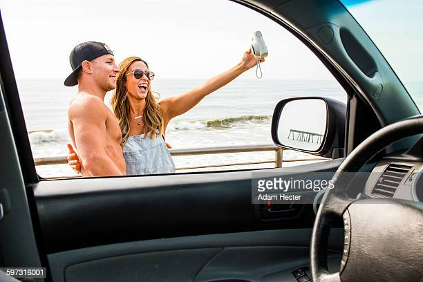 Caucasian couple taking selfie at beach
