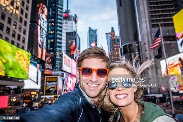 caucasian couple taking selfie in times square, new york city, new york, united states - escapada urbana fotografías e imágenes de stock