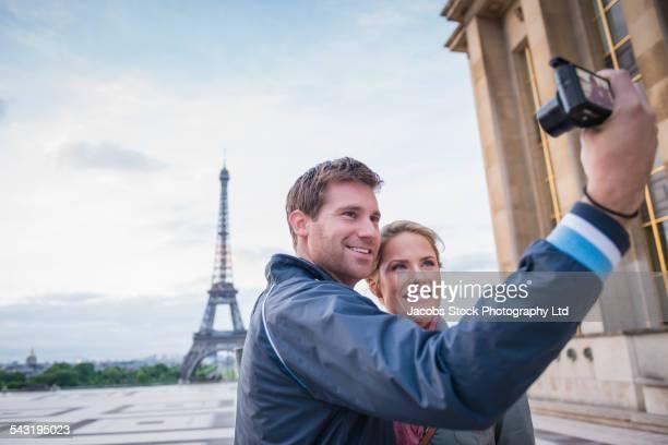 Caucasian couple taking selfie near Eiffel Tower, Paris, France