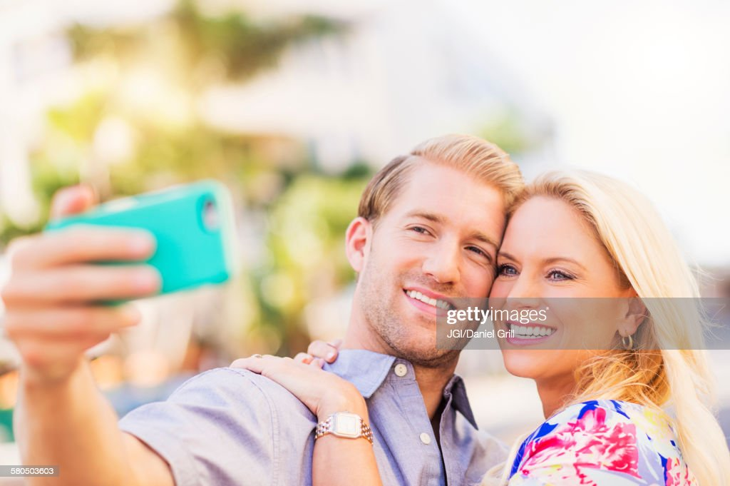 Caucasian couple taking selfie on cell phone : Stock Photo