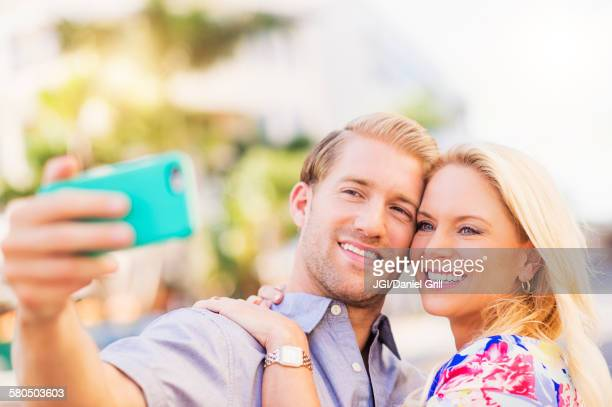 caucasian couple taking selfie on cell phone - gigolo photos et images de collection