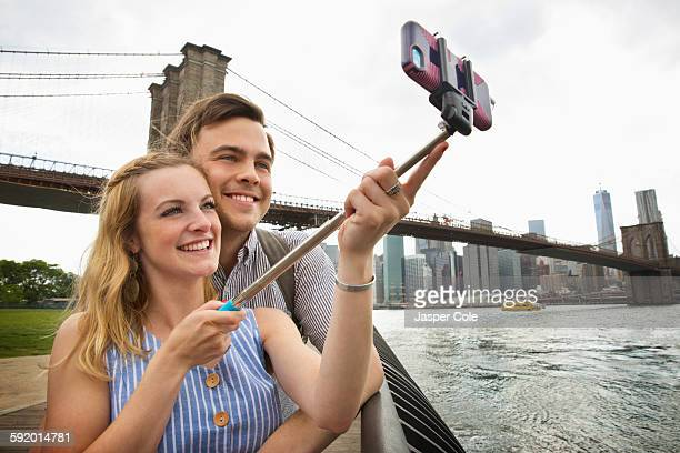 Caucasian couple taking selfie with cell phone under Brooklyn Bridge, Brooklyn, New York, United States