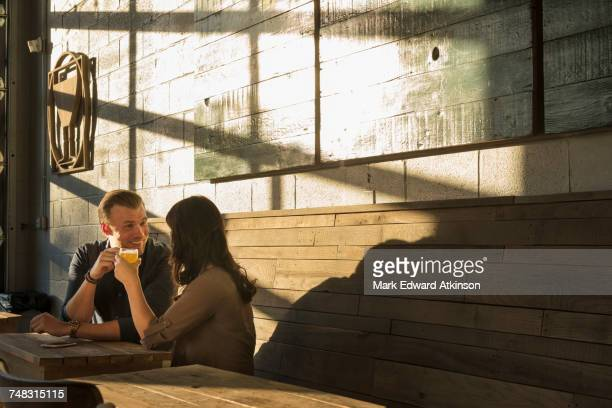 Caucasian couple talking in brew pub