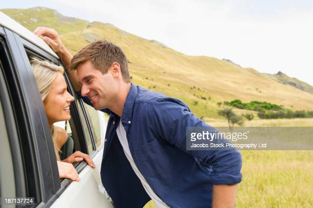 caucasian couple talking in car - leaning stock pictures, royalty-free photos & images