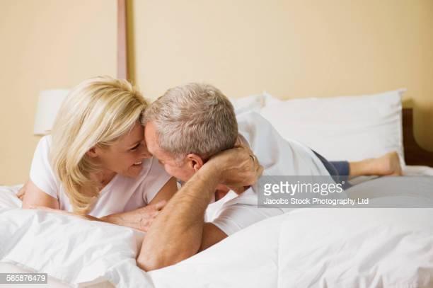 caucasian couple talking on bed - ouder volwassenen koppel stockfoto's en -beelden