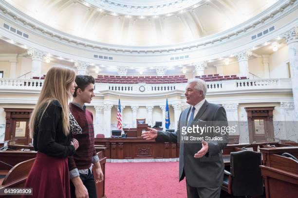 caucasian couple talking to politician in capitol building - governor stock pictures, royalty-free photos & images