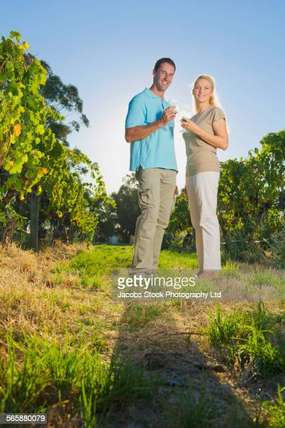 Caucasian couple tasting wine in vineyard