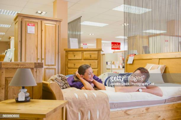 Caucasian couple testing mattress in furniture store