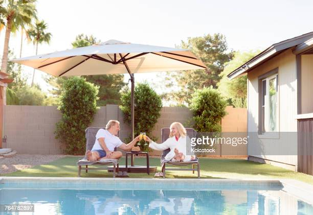 caucasian couple toasting near swimming pool - sunshade stock pictures, royalty-free photos & images