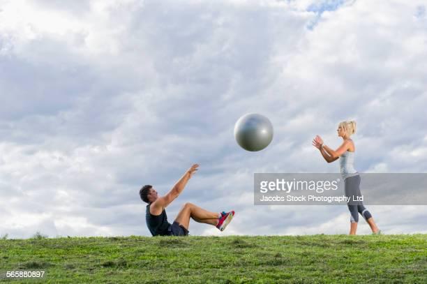 caucasian couple tossing fitness ball in grass field - homem pegando mulher imagens e fotografias de stock