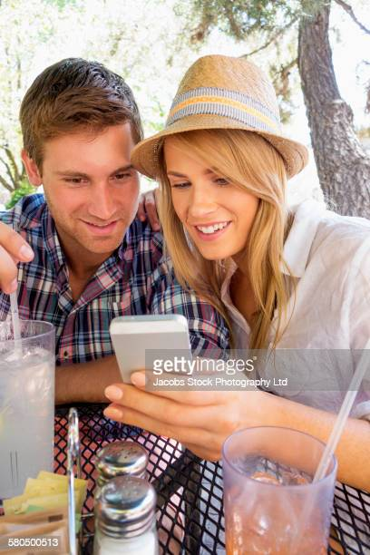 Caucasian couple using cell phone at table with beverages