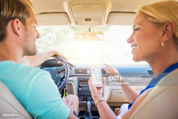 Caucasian couple using cell phone navigation in car