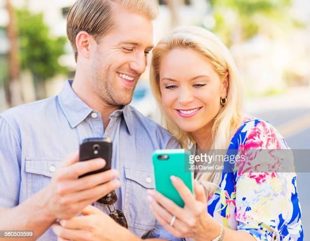 caucasian couple using cell phones - cougar woman fotografías e imágenes de stock