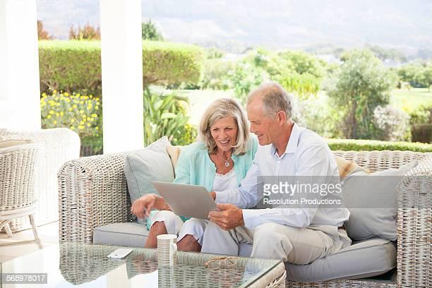 Caucasian couple using digital tablet on sofa outdoors