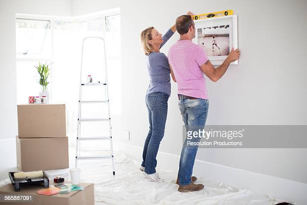 caucasian couple using level in new home - hanging stock pictures, royalty-free photos & images