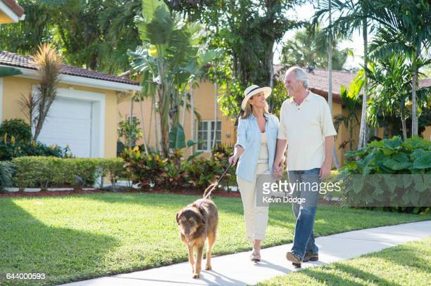 Caucasian couple walking dog in neighborhood