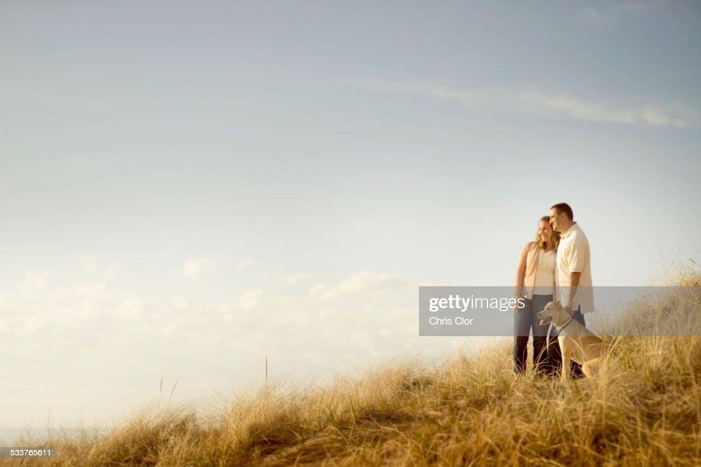 Caucasian couple walking dog on grassy dunes : Foto stock