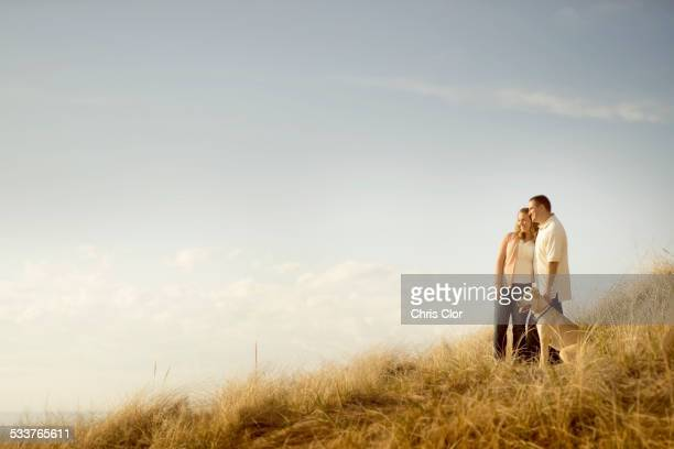 Caucasian couple walking dog on grassy dunes