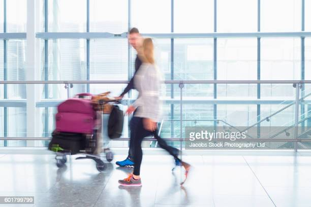 Caucasian couple walking in airport