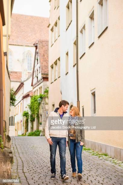 Caucasian couple walking in city