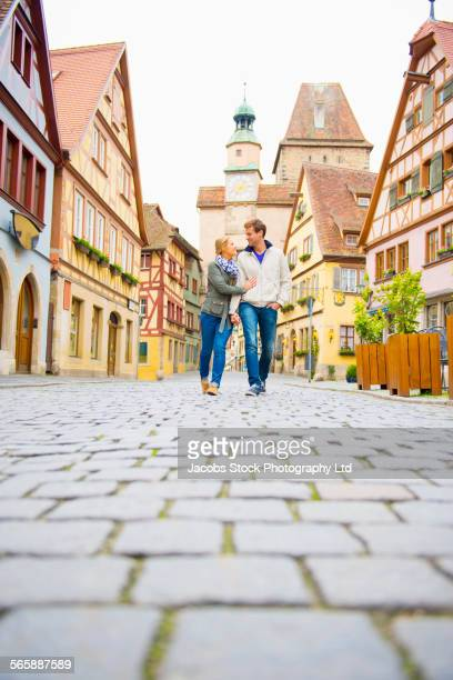 Caucasian couple walking in city