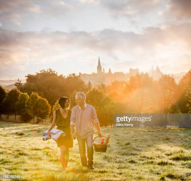 Caucasian couple walking in field carrying picnicblanket and basket