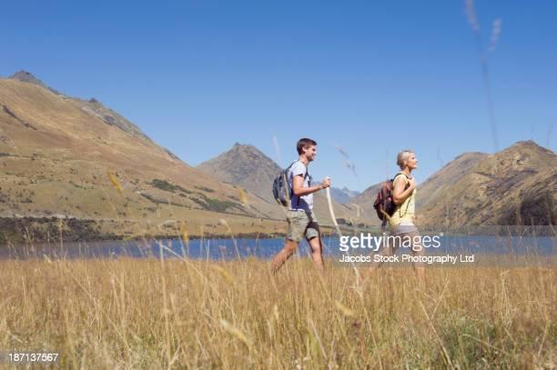 Caucasian couple walking in rural landscape