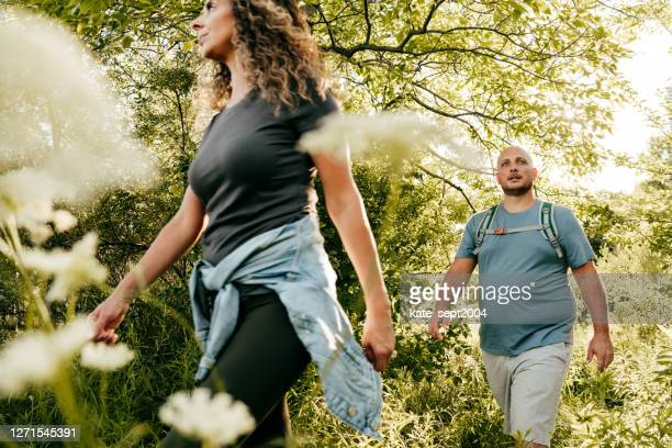 caucasian couple walking in the park. young woman and overweight man walking through the woods. - overweight stock pictures, royalty-free photos & images
