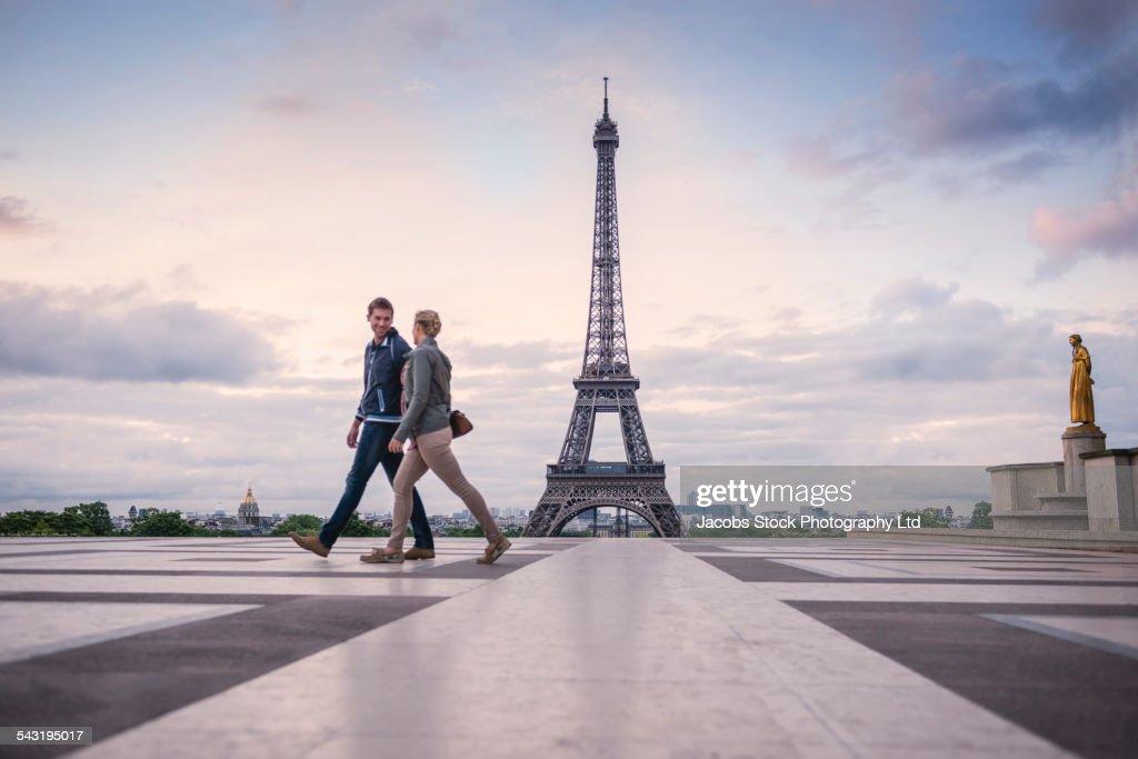 Caucasian couple walking near Eiffel Tower, Paris, France : Stock Photo