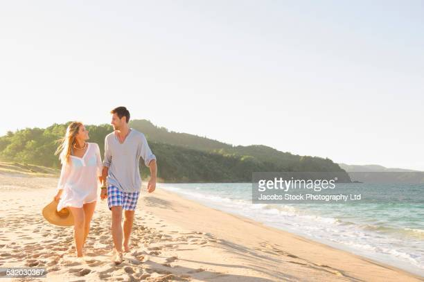 caucasian couple walking on beach - northland new zealand stock pictures, royalty-free photos & images