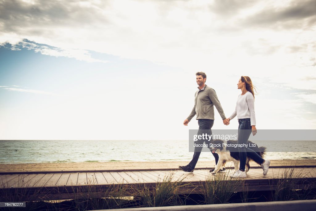 Caucasian couple walking on boardwalk with the dog : Stock Photo