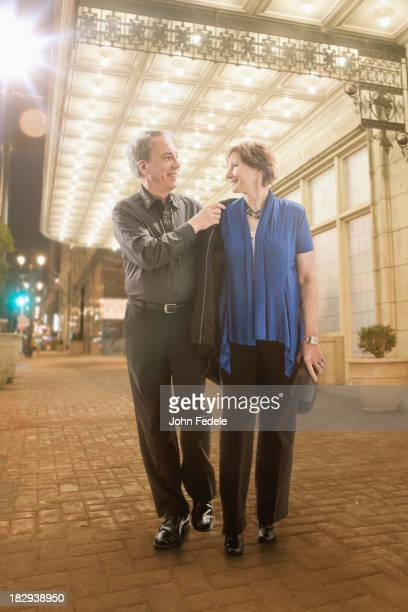 Caucasian couple walking on city street