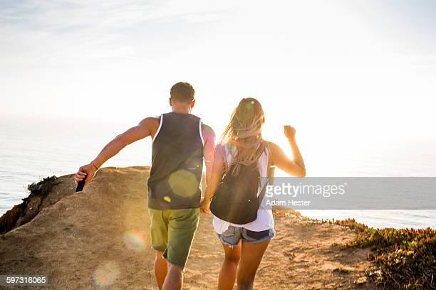 Caucasian couple walking on cliff