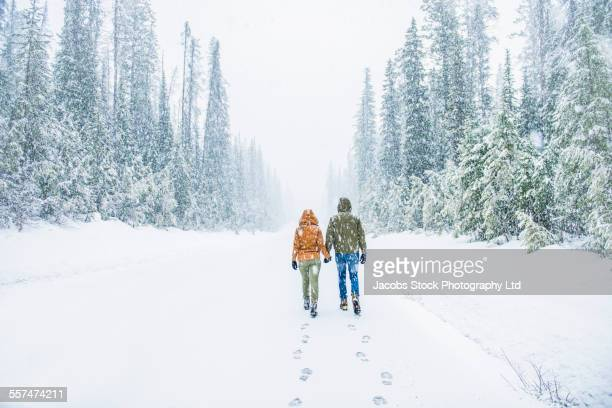 Caucasian couple walking on snowy forest road