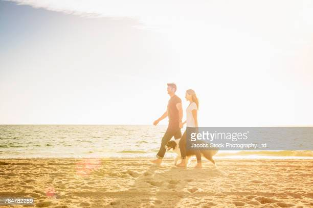 Caucasian couple walking on the beach with dog