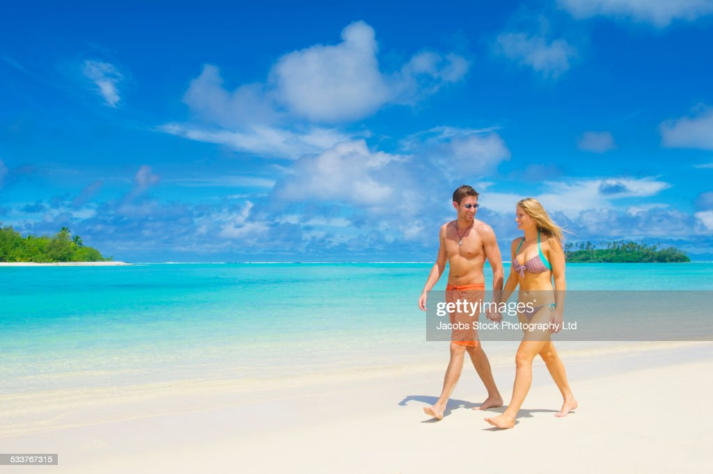 Caucasian couple walking on tropical beach : Foto stock