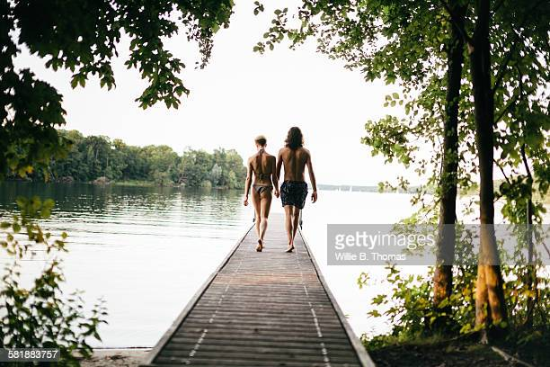 Caucasian Couple walking on wooden dock over lake