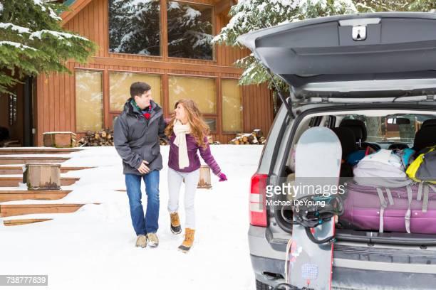 Caucasian couple walking to car at winter resort
