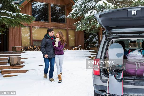 Caucasian couple walking to car with snowboards in winter