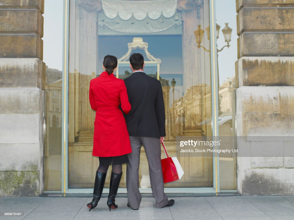Caucasian couple window shopping on city sidewalk : Stock Photo