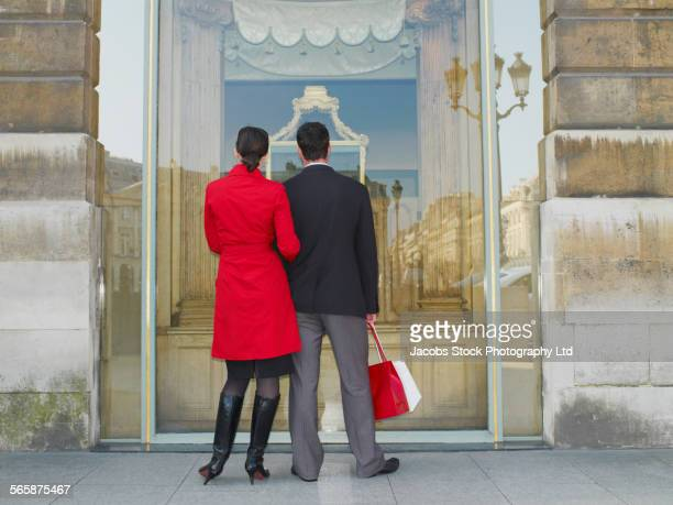 Caucasian couple window shopping on city sidewalk