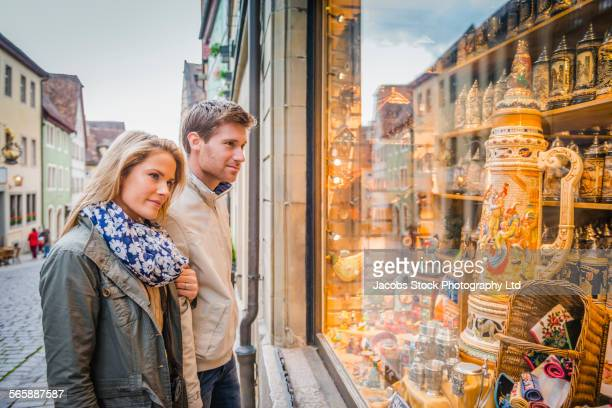 caucasian couple window shopping on sidewalk - rothenburg stock photos and pictures