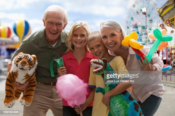 Caucasian couple with grandchildren at amusement park
