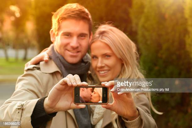 Caucasian couple with picture of themselves kissing